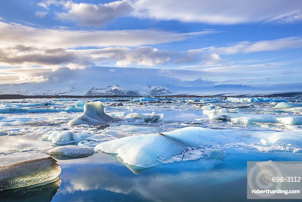 Mountains behind icebergs locked in the frozen water of Jokulsarlon Lagoon, Jokulsarlon, southeast Iceland, Iceland, Polar Regions