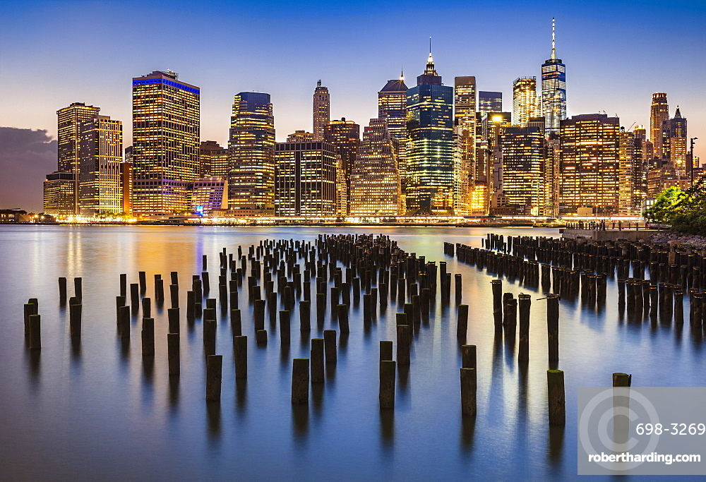 Lower Manhattan skyline, New York skyline, exposed wooden pier stumps, at night, East River, New York, United States of America, North America