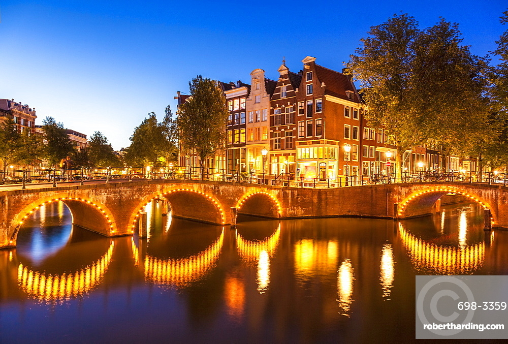 Illuminated bridges and reflections at night, Keizergracht and Leilesgracht canals, Amsterdam, North Holland, Netherlands, Europe