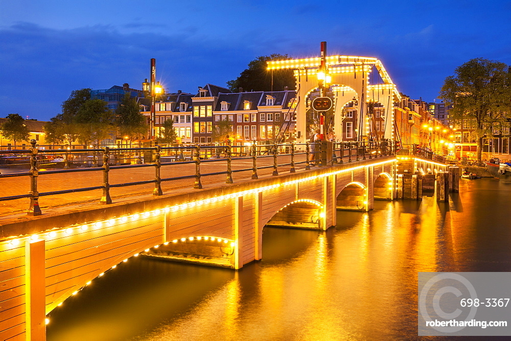 Illuminated Magere brug (Skinny Bridge) at night spanning the River Amstel, Amsterdam, North Holland, Netherlands, Europe