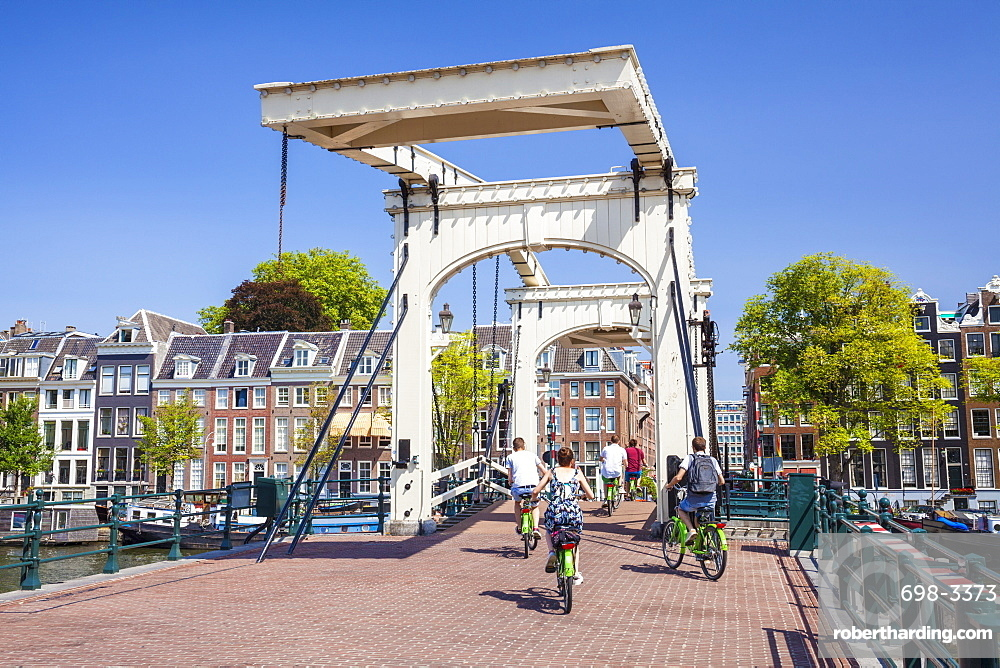 Cyclists riding across the Magere brug (Skinny Bridge) spanning the River Amstel, Amsterdam, North Holland, Netherlands, Europe