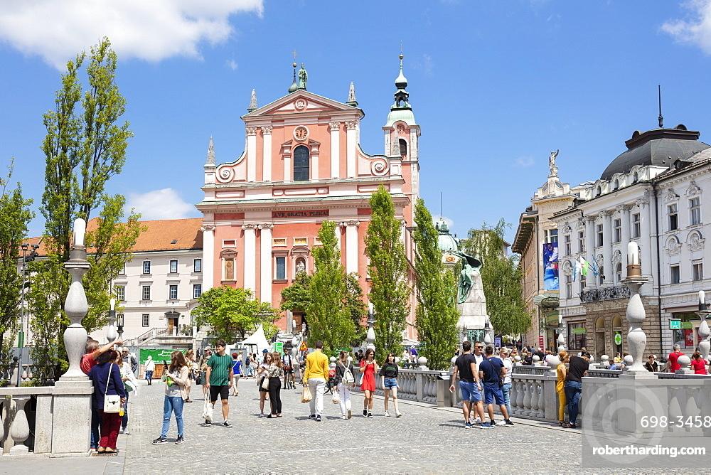 The Pink Franciscan Church in Preseren square and tourists walking over the triple bridge central Ljubljana Slovenia EU Europe