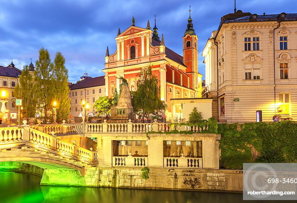 The pink Franciscan Church and the Triple Bridge (Tromostovje) over the Ljubljanica Rriver at night, Ljubljana, Slovenia, Europe