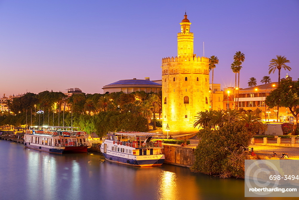 Tour boats moored on the Guadalquivir river near the Torre del Oro at sunset, Seville, Andalusia, Spain, Europe