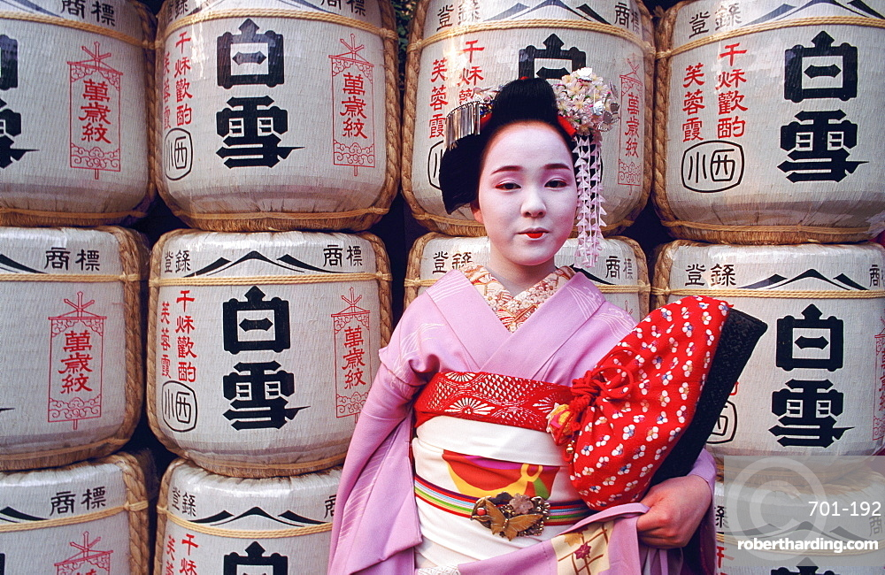 Portrait of a Maiko (a geisha's apprentice) in front of temple lanterns, Kyoto, Japan