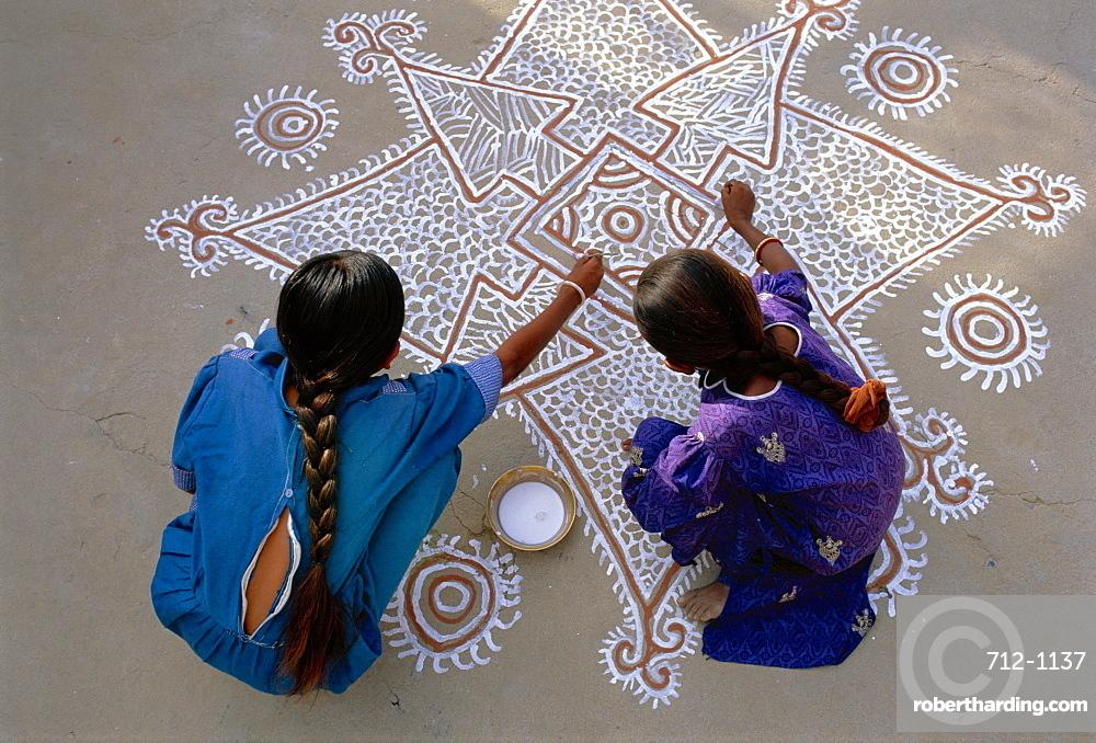 Women painting a Mandana on the ground, Village near Jodhpur, Rajasthan, India