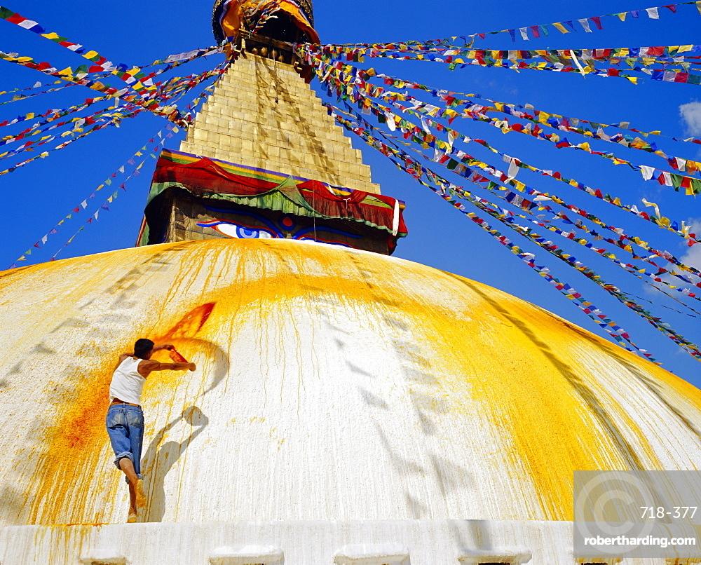 Young man throwing saffron water on the stupa in order to purify it before ritual, Bodhnath, Katmandu, Nepal