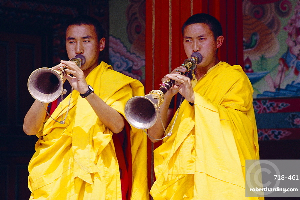 Monks blowing flutes outside a gompa (Tibetan monastery), Bodhnath, Katmandu, Nepal