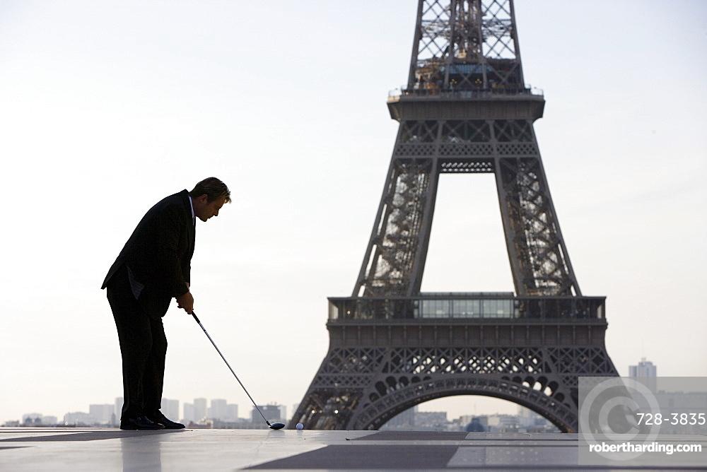 Business man playing golf near the Eiffel Tower, Paris, France, Europe