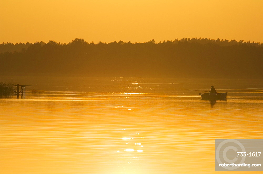 Sunset on lake and fishing boat, Aukstaitija National Park, Lithuania's first national park, Lithuania, Baltic States, Europe