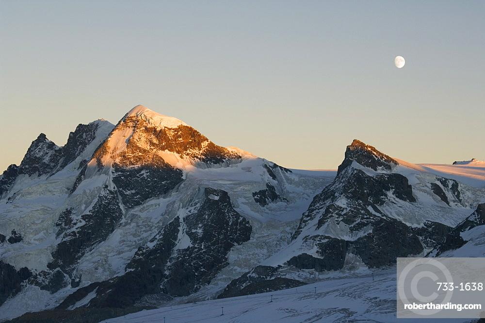 Moon rising over the Klein Matterhorn, 3883m and Breithorn 4164m mountains, Zermatt Alpine Resort, Valais, Switzerland, Europe