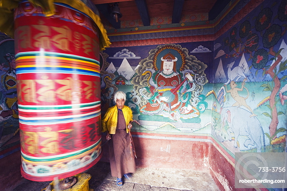 A woman spinning a prayer wheel, Chimi Lhakhang dating from 1499, Temple of the Divine Madman Lama Drukpa Kunley, Punakha, Bhutan, Asia