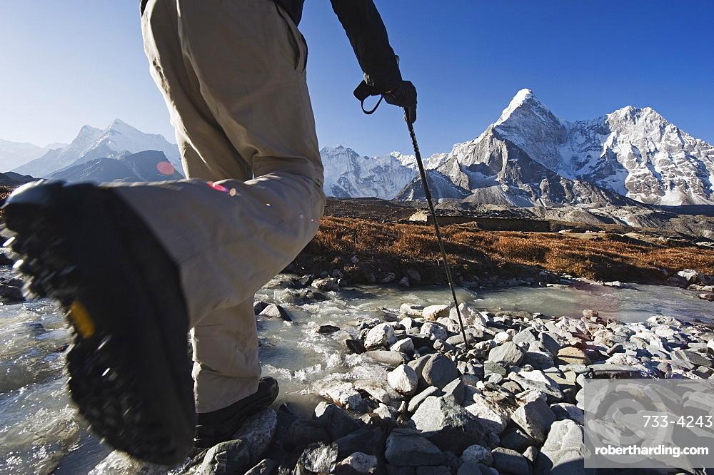 Trekker crossing a mountain stream, Ama Dablam, 6812m, Solu Khumbu Everest Region, Sagarmatha National Park, Himalayas, Nepal, Asia