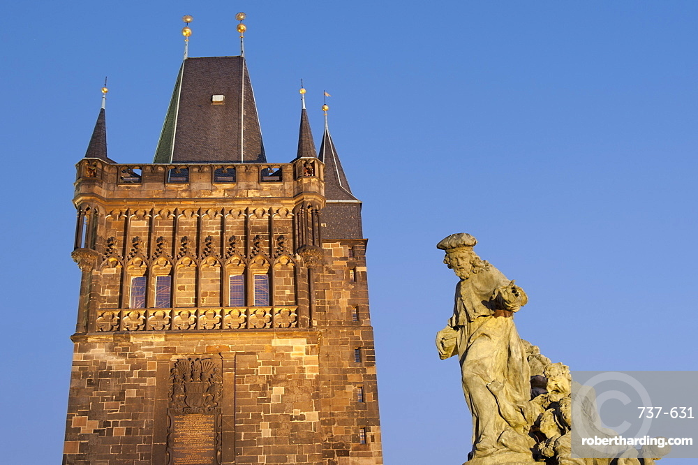 Gothic Old Town Bridge Tower and Baroque statue of St. Ivo (Bishop of Chartres) at twilight, Charles Bridge, Old Town, UNESCO World Heritage Site, Prague, Czech Republic, Europe