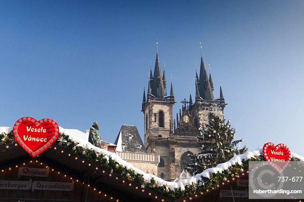 Merry Christmas sign at snow-covered Christmas Market and Tyn Church, Old Town Square, Prague, Czech Republic, Europe
