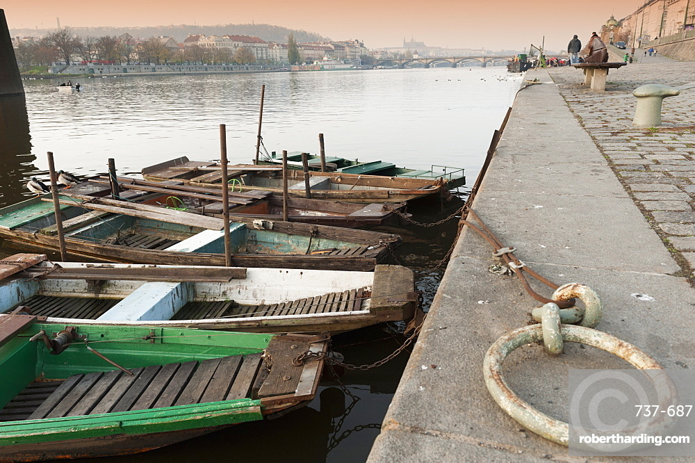 Fishing boats, ducks, Vltava River and Prague Castle during autumn at embankment below Rasinovo nabrezi, Vyton, Nove Mesto, Prague, Czech Republic, Europe