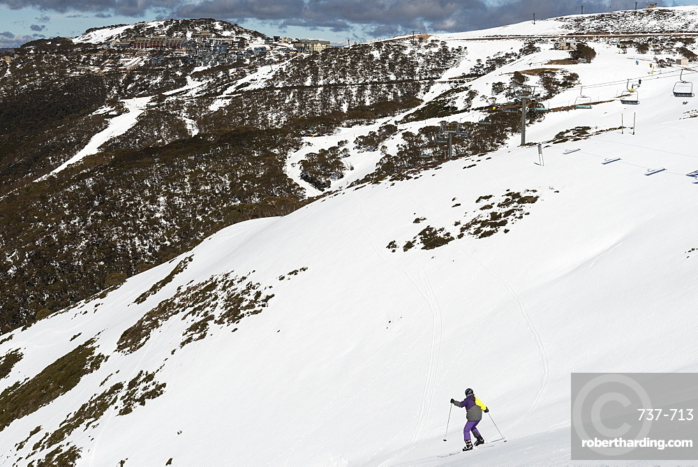 Young skier skiing down The Chute and Mount Hotham Village, Mount Hotham, Victoria, Australia, Pacific