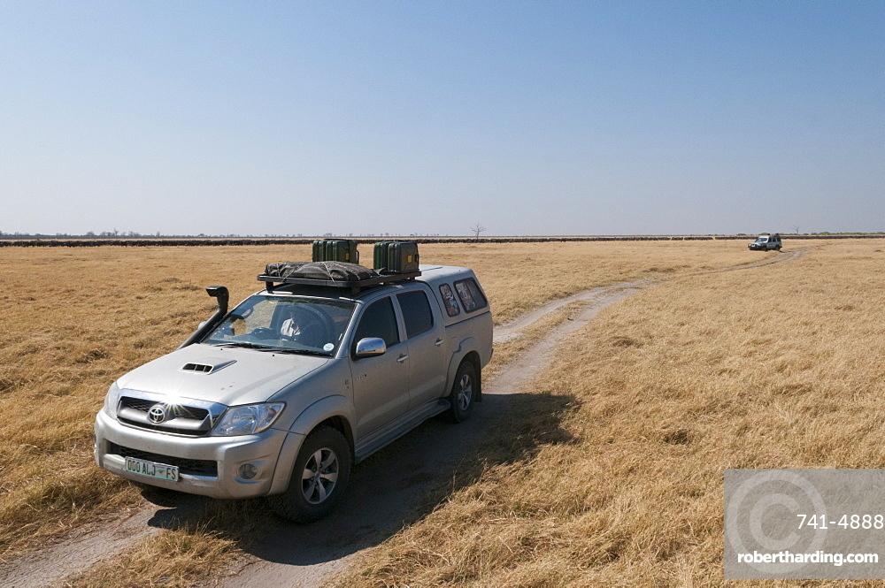 Off-road vehicles driving close to African buffalo herd, Savuti Marsh, Chobe National Park, Botswana, Africa