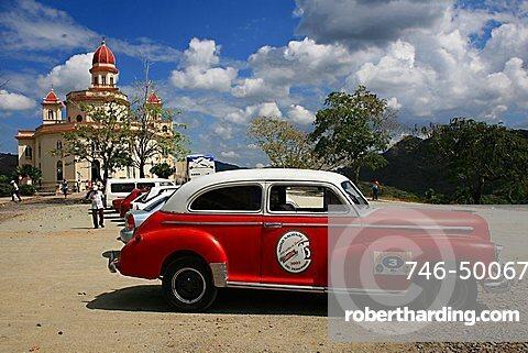 Vintage car in front of Virgen de la Caridad del Cobre sanctuary, Santiago de Cuba, Cuba, West Indies, Central America