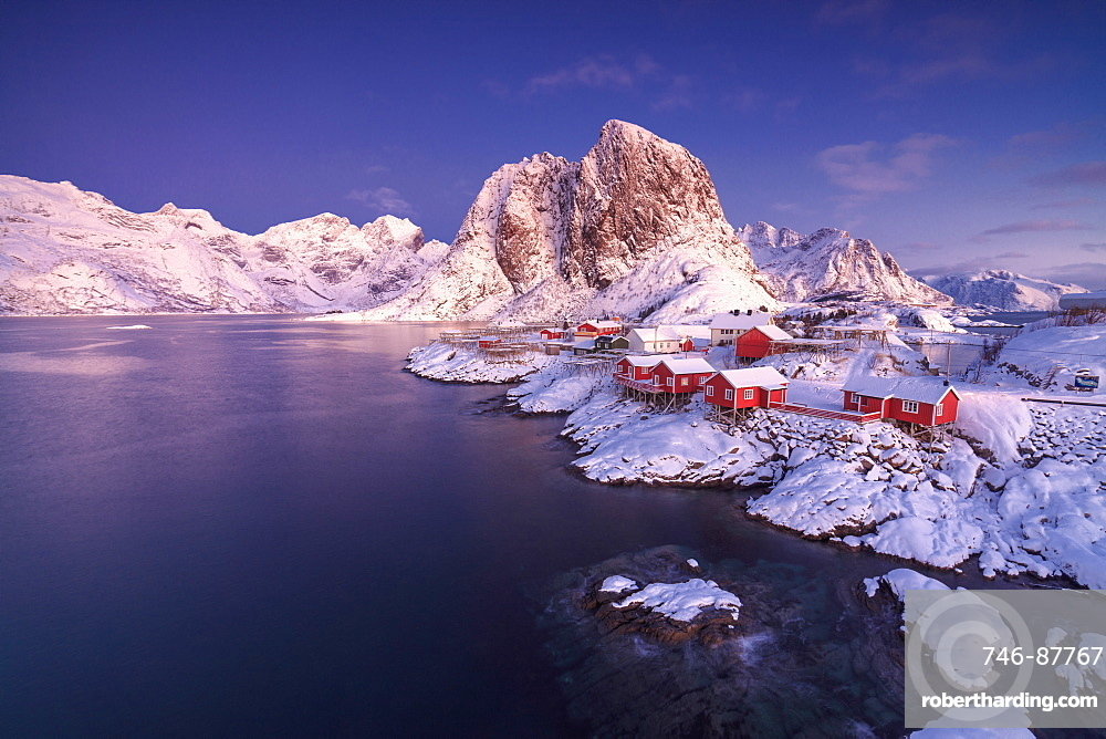 The colors of dawn on snowy peaks and the frozen sea around the fishing village Hamnoy Nordland, Lofoten Islands, Norway, Europe