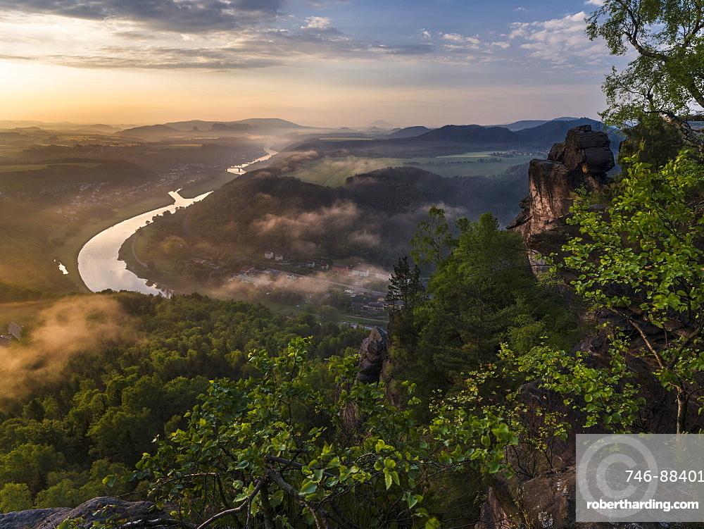 Elbe Sandstone Mountains (Elbsandsteingebirge) in the NP  Saxon Switzerland (Saechsische Schweiz) during spring. Valley of river Elbe with spa Bad Schandau during sunrise. Europe, Central Europe, Germany, Saxony, May