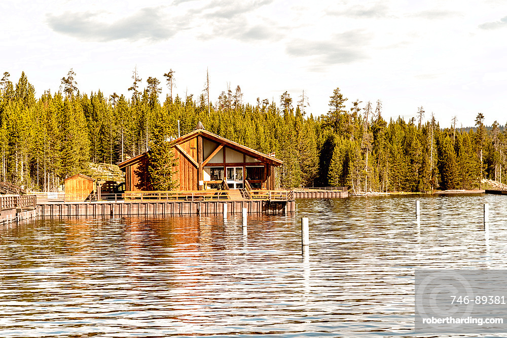 Wooden homr on Yellowstone Lake with trees water reflections.