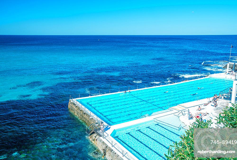 Swimmers enjoy beautiful pool along the sea.