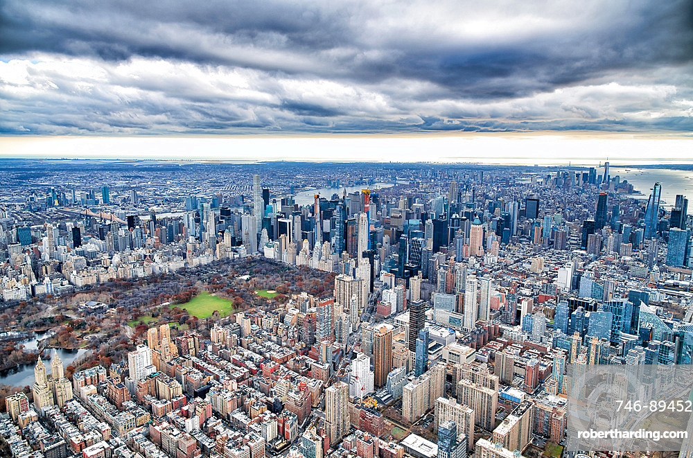 New York City from helicopter point of view. Central Park and Manhattan skyscrapers on a cloudy day, USA