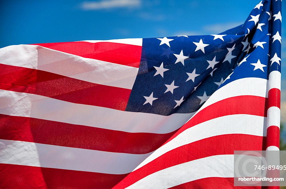 Waving American Flag on blue sky background.