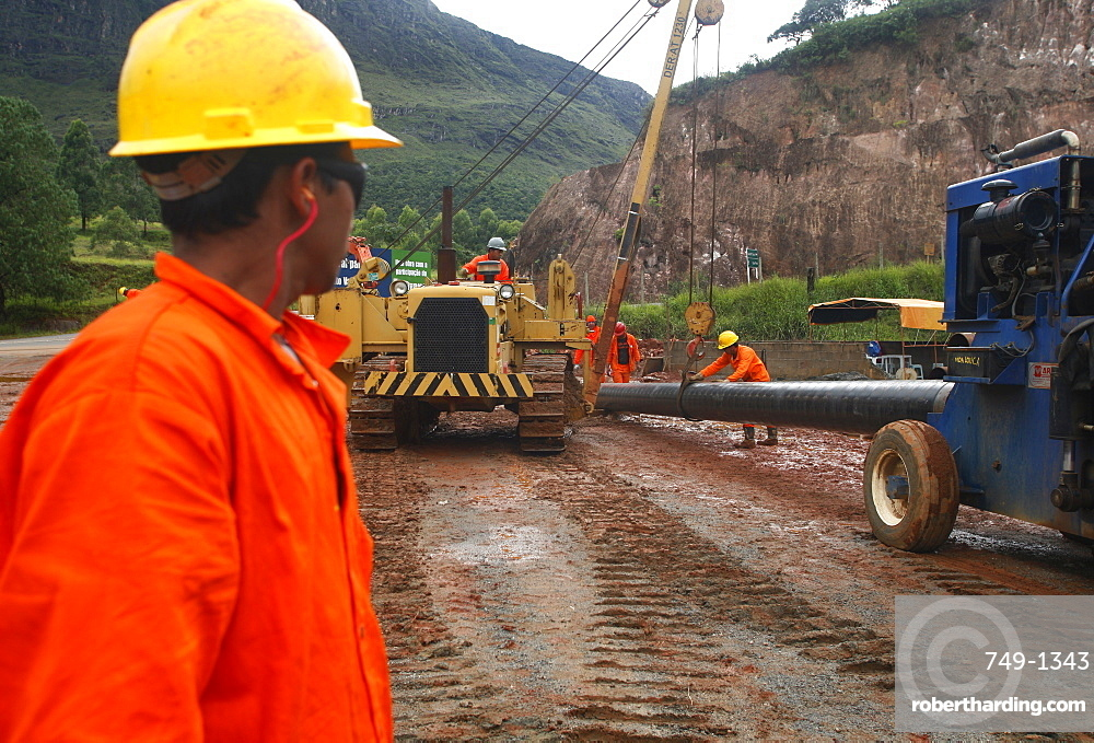 Workers putting pipes for natural gas near Congonhas, Minas Gerais, Brazil, South America