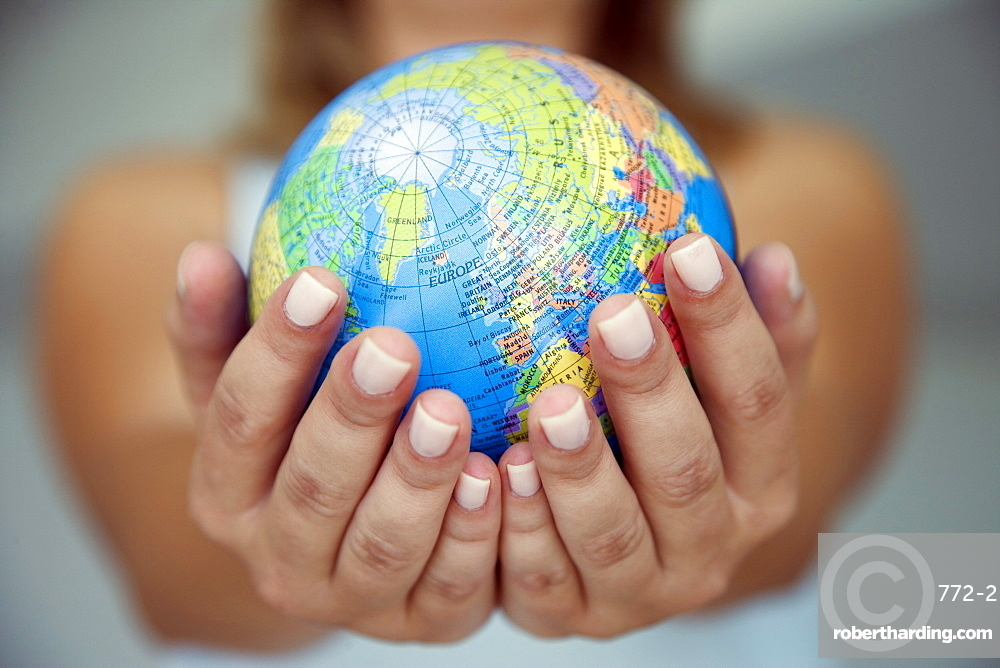 Woman's hands holding world globe