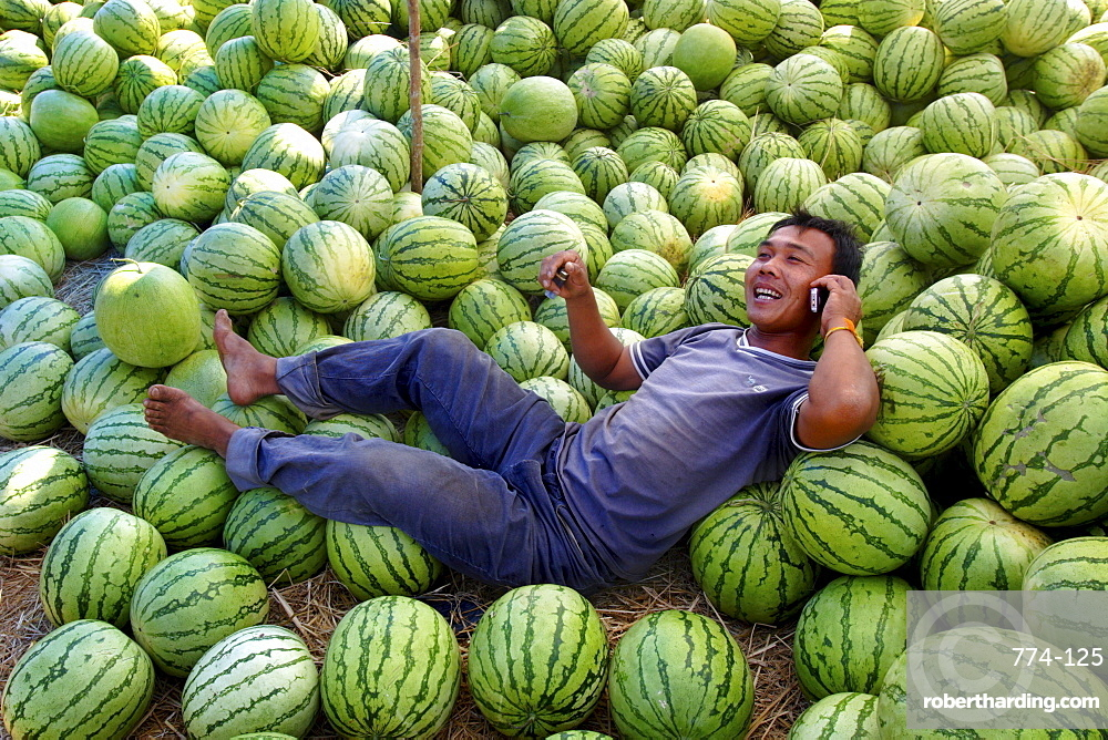 A man talks on his mobile phone under the shade of his watermelon stall, Savannakhet, Laos, Indochina, Southeast Asia, Asia