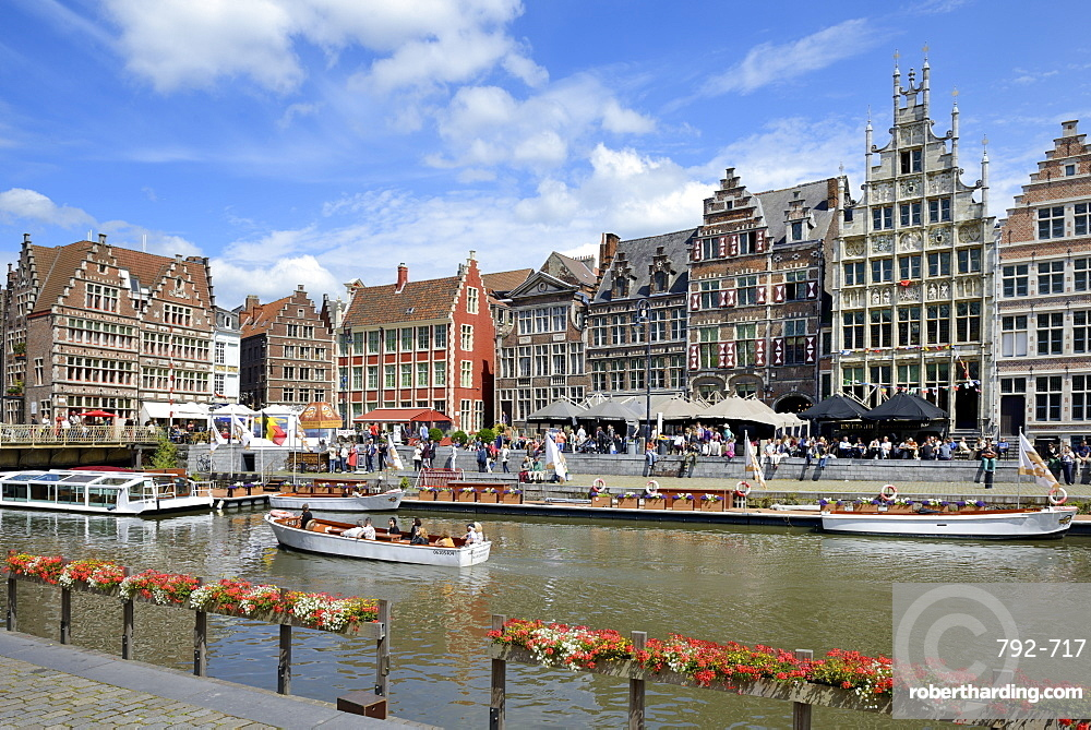 Tourists in sightseeing boats on River Leie and Medieval guild houses on Graslei Quay, Ghent, Flanders, Belgium, Europe