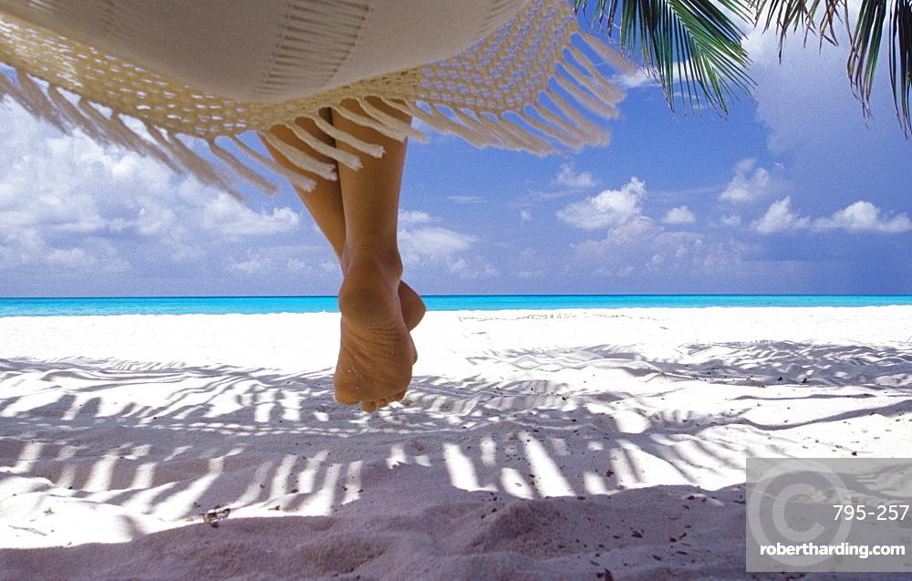 Woman sitting on a hammock overlooking sea, The Maldives, Indian Ocean, Asia