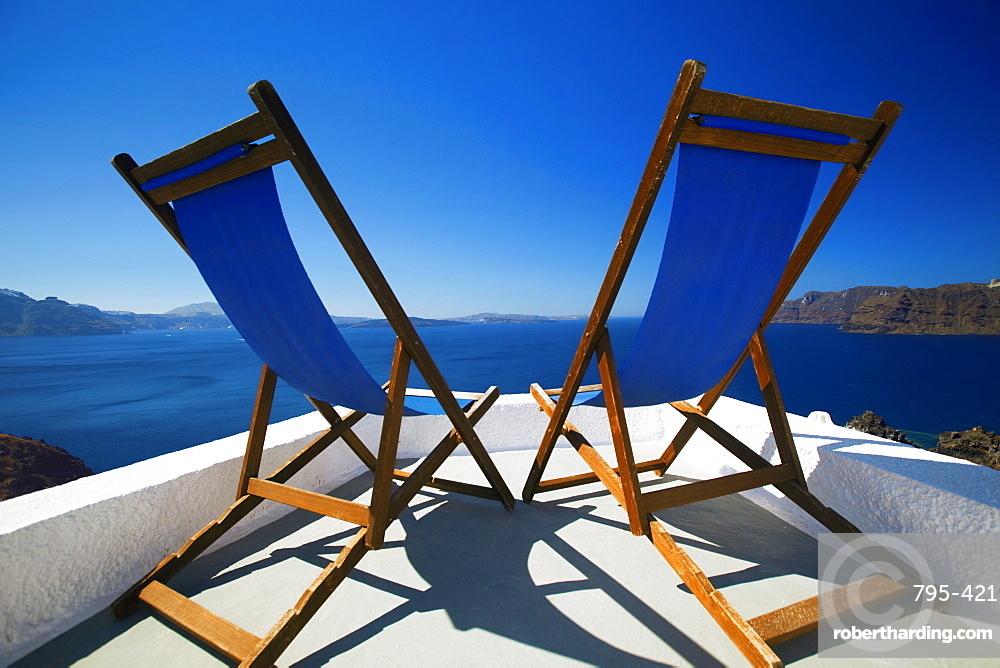 Deck chairs on terrace overlooking ocean, Santorini, Cyclades, Greek Islands, Greece, Europe