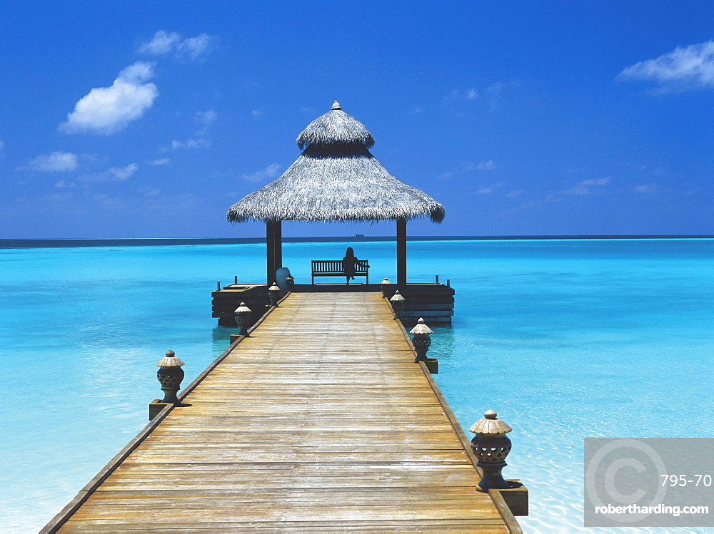 Young woman sitting on bench at the end of jetty, Maldives, Indian Ocean, Asia