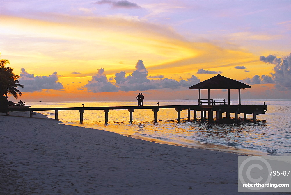 Couple on jetty looking at sunset, Maldives, Indian Ocean, Asia