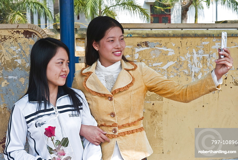Vietnam, People, Two Young Ladies taking a picture of them selves with a camera phone.