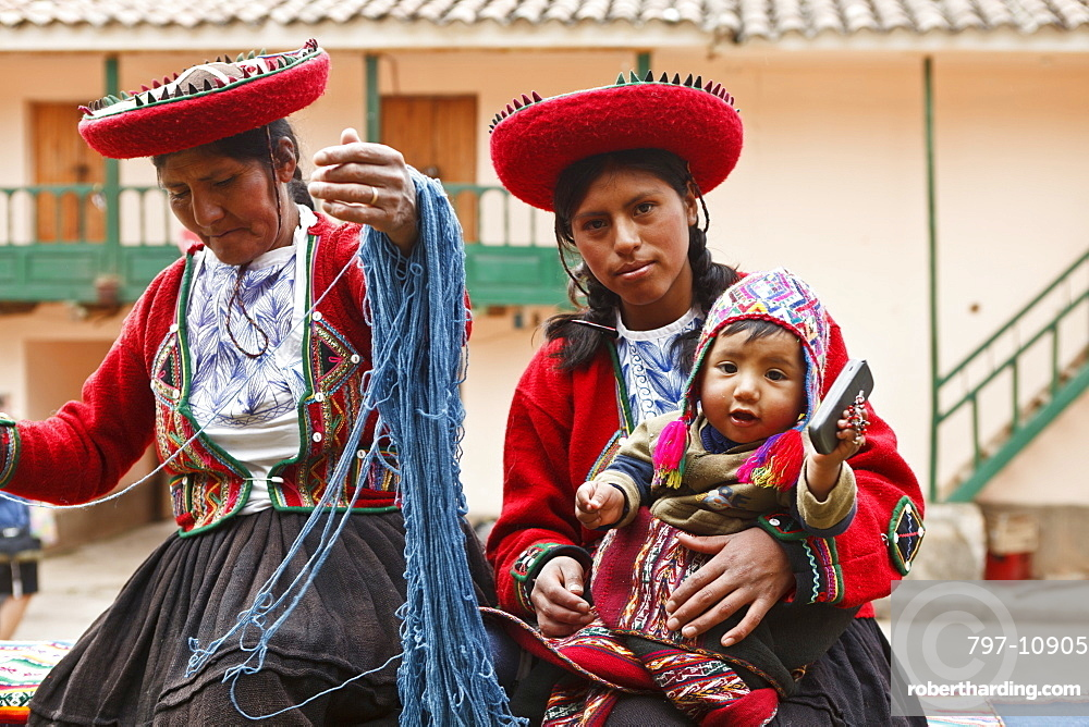 Peru, Indigenous People, Mother and baby in traditional dress with a lady making yarn and infant holding mobile phone.