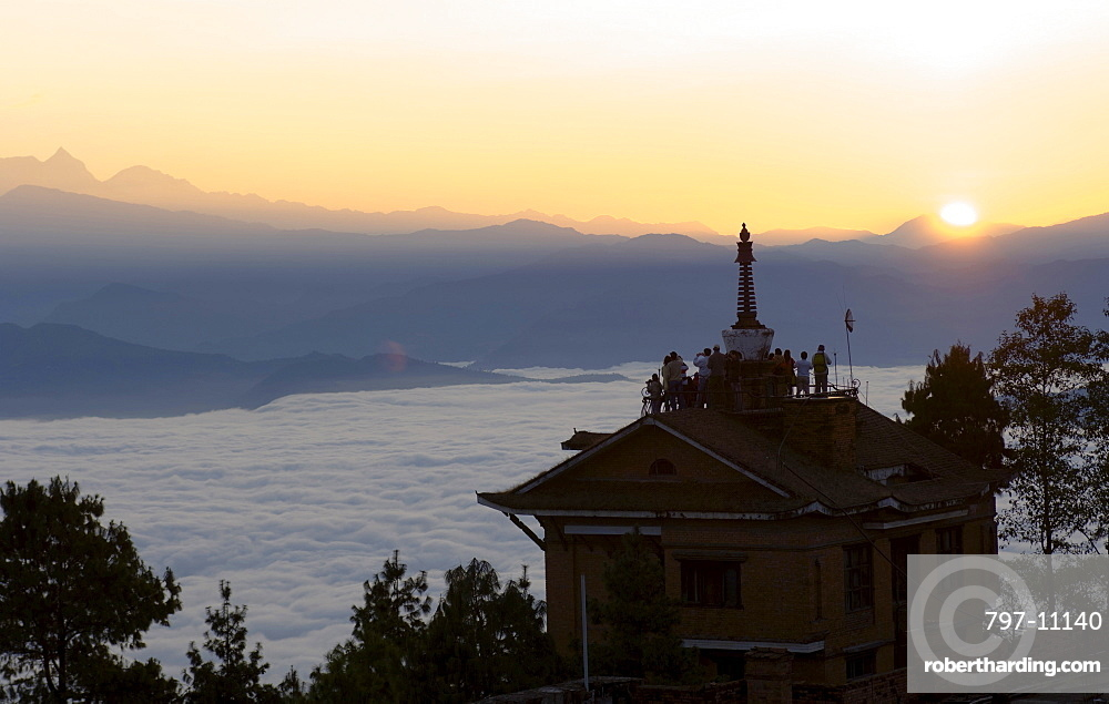 Nepal, Nagarkot, Sunrise view across clouded valley towards Himalayan mountains with Buddhist Stupa on top of building.