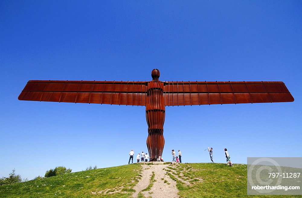 England, Tyne and Wear, Gateshead, Angel Of The North Against Deep Blue Sky Steel Sculpture By Antony Gormley Standing 20 Metres Tall With Wingspan Of 54 Metres Constructed From Steel Showing Tourists For Scale Against A Deep Blue Sky.