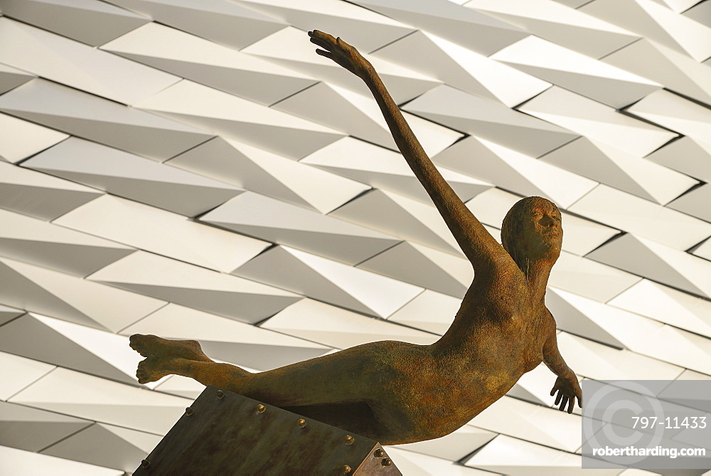 Ireland, North, Belfast, Titanic Quarter, Titanic Belfast Visitor Experience, 'Titanica' sculpture by Rowan Gillespie with section of the building in the background.