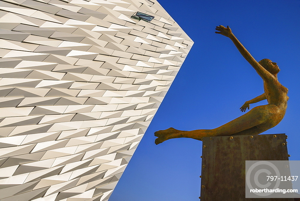 Ireland, North, Belfast, Titanic Quarter, Titanic Belfast Visitor Experience, 'Titanica' sculpture by Rowan Gillespie with a section of the building and blue sky in the background.