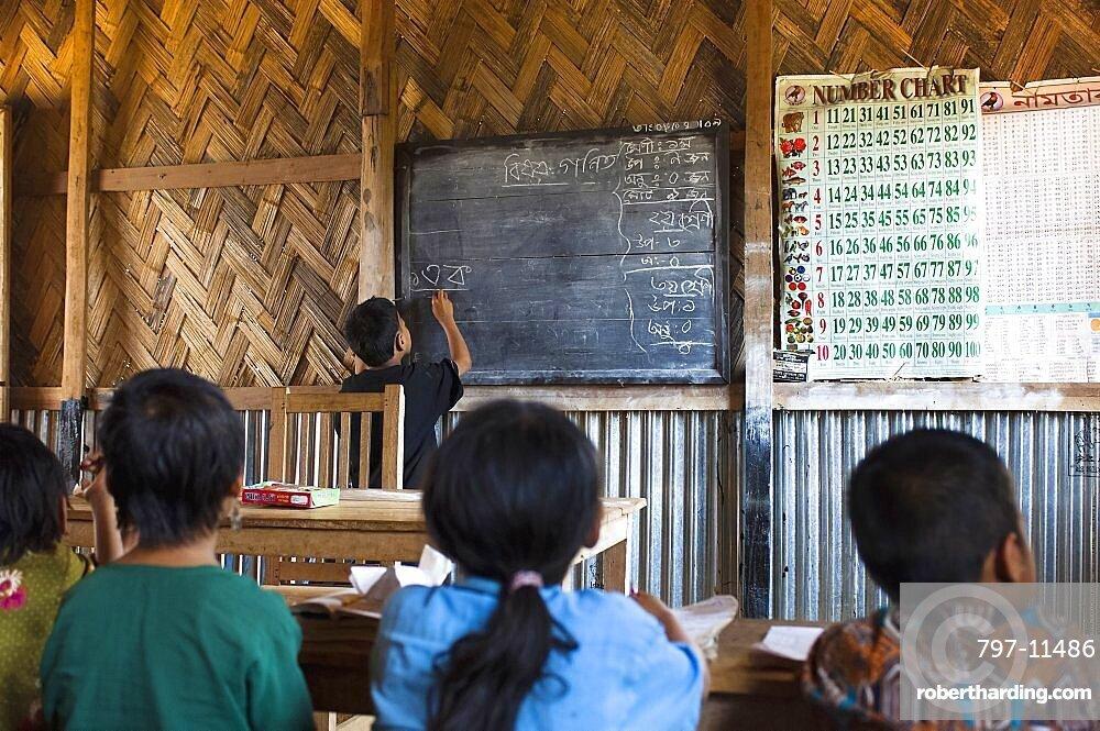 Bangladesh, Chittagong Division, Bandarban, School boy writing Bangladeshi on the blackboard in a UN supported primary school classroom.