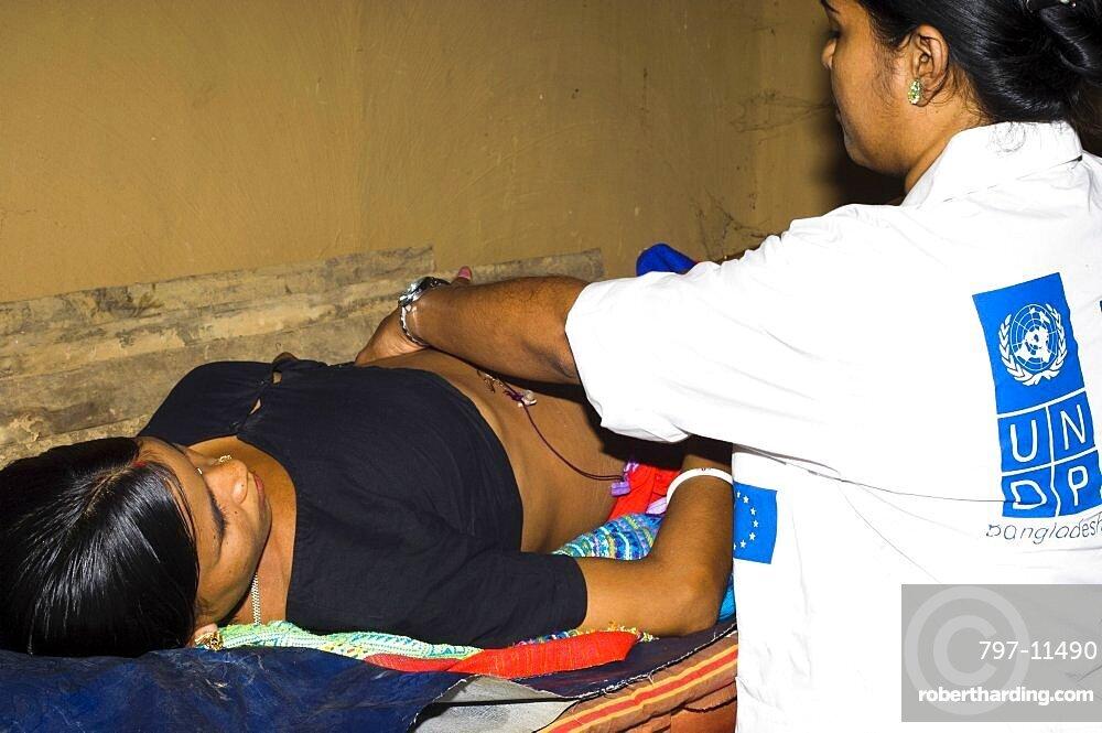 Bangladesh, Chittagong Division, Khagrachari, Pregnant mother being examined by UNDP nurse.