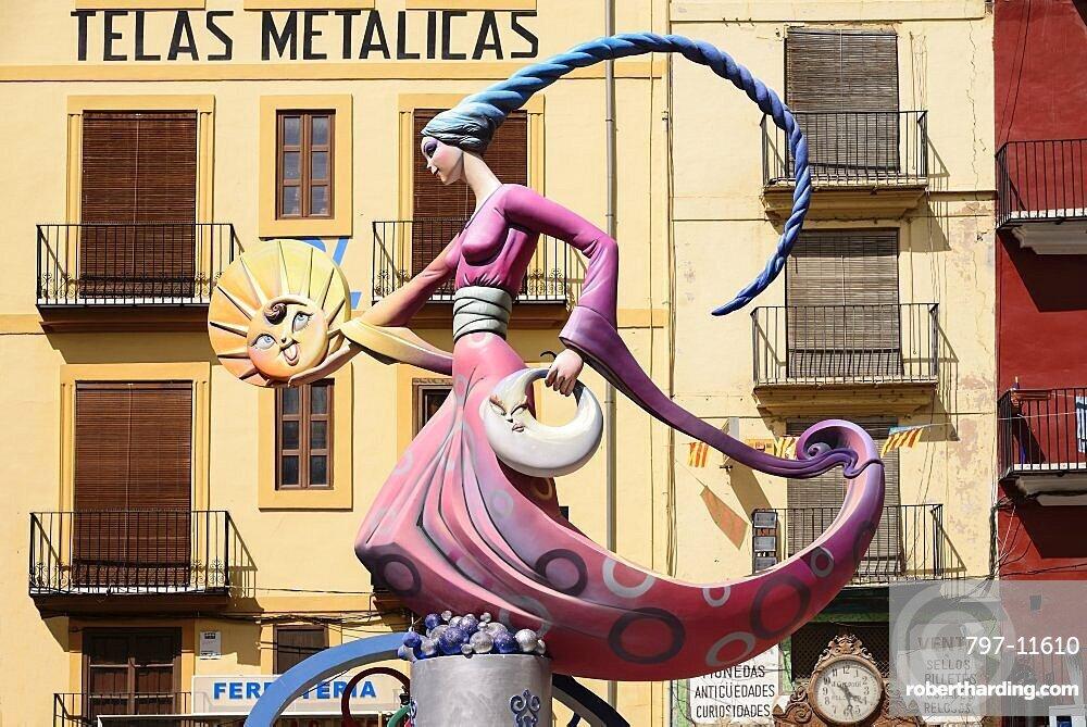 Spain, Valencia Province, Valencia, Papier Mache figure of a lady in a pink dress holding a replica of the sun during Las Fallas festival.