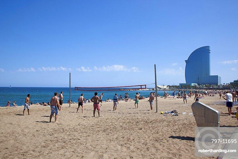 Spain, Catalonia, Barcelona, Playa de St Sebastia, Barceloneta Beach, people playing volleyball with the W hotel behind.