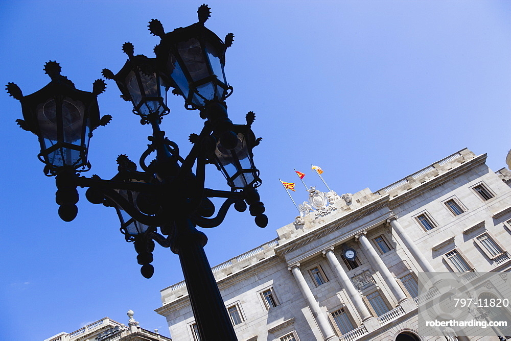 Spain, Catalonia, Barcelona, The Neo-Classical town hall Casa de la Ciutat in Placa de Sant Jaume in the Gothic Quarter with an ornate street light in the foreground.