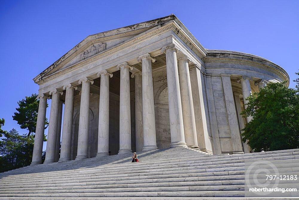 USA, Washington DC, National Mall, Thomas Jefferson Memorial, a lone tourist sitting on the steps beneath the facade.
