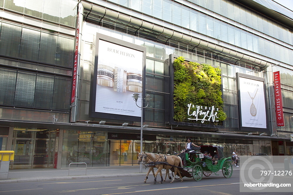 Germany, Berlin, Mitte, Vertical planting on the exterior of Galeries Lafayette on Friedrichstrasse with horse and carriage passing.